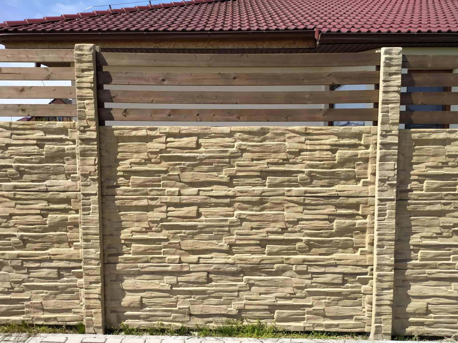 betonový plot s pískovou barvou a plotovkami